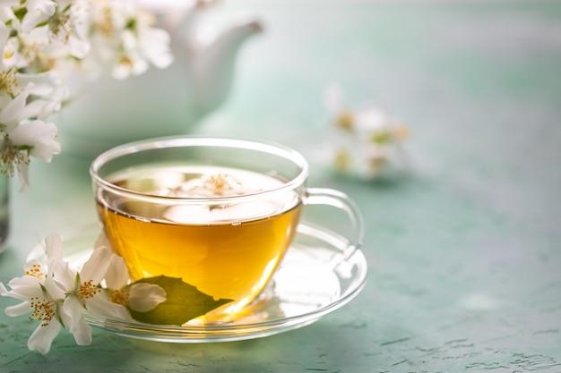 Jasmine flower tea on green stone, spa concept. copy space.