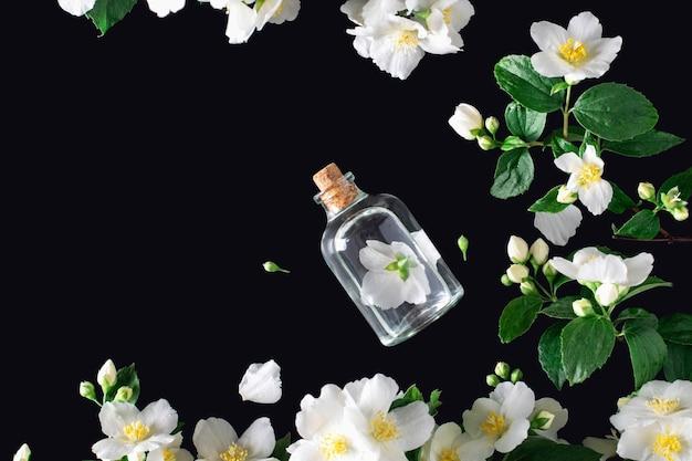 Цветок жасмина с бутылкой эссенции над черным