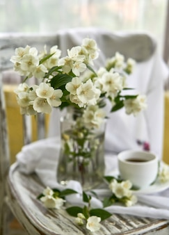 Jasmine flowers in a glasse vase. stillife with jasmine and cup of coffee.