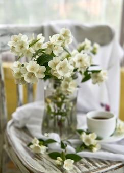 Цветы жасмина в стеклянной вазе. натюрморт с жасмином и чашкой кофе.