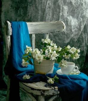 白い花瓶にジャスミンの花。ジャスミンと一杯のコーヒーとスティリフェ。