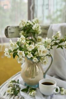 Цветы жасмина в белой вазе. натюрморт с жасмином и чашкой кофе.