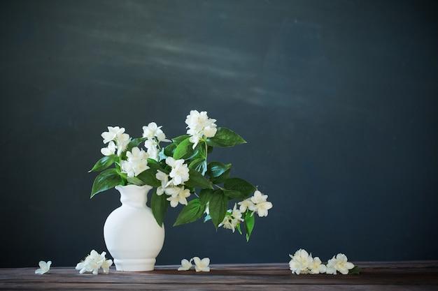 Цветы жасмина в керамической вазе на белом фоне