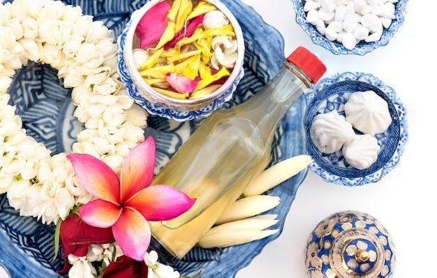 재스민 화환과 물, 향수, marly 석회암, 송크란 축제 또는 태국 새해를 위해 절연 된 파이프 건을 장식하고 향기로운 물 그릇에 다채로운 꽃.