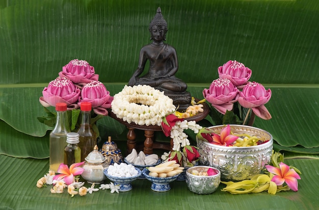 Jasmine garland and colorful flower in water bowls decorating and scented water, perfume, marly limestone, pipe gun on banana leaf for songkran festival or thai new year.