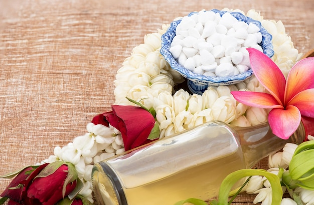 Jasmine garland and colorful flower in water bowls decorating and scented water, perfume, marly limestone, pipe gun isolated on an old wood  for songkran festival or thai new year.