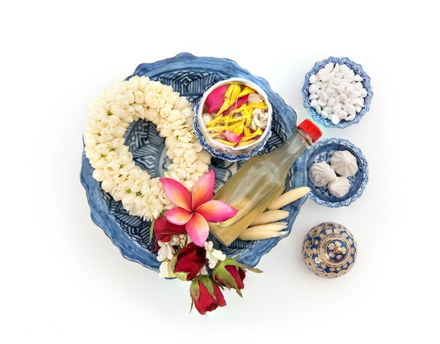 Jasmine garland and colorful flower in water bowls decorating and scented water, perfume, marly limestone, pipe gun isolated on  for songkran festival or thai new year.