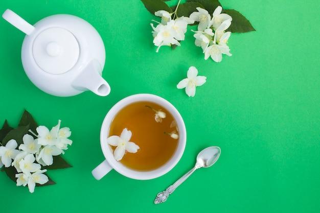 Зеленый чай с жасмином в белой чашке на зеленой поверхности