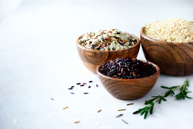 Jasmine rice, brown, black and red rice. mixed assortment of grains in wooden bowls on grey concrete, copy space