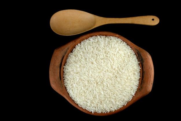 진흙 냄비에 재스민 쌀과 검은 배경에 고립 된 나무 국자