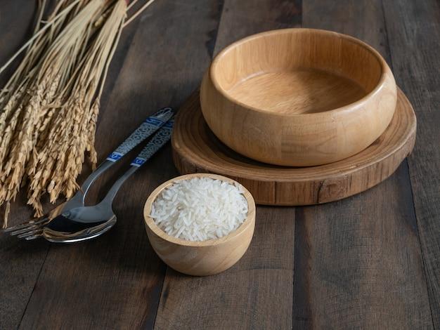 コピースペースとグランジ木製テーブルの背景に木製のボウルとスプーンでジャスミンライス