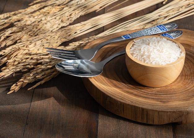 コピースペース、上面図とグランジ木製テーブルの背景にスプーンで木製のボウルにジャスミンライス