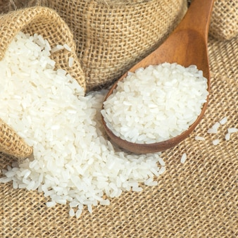 Jasmine rice on wooden scoop with burlap sack