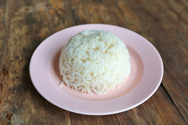 Jasmine rice in pink plate on wooden table