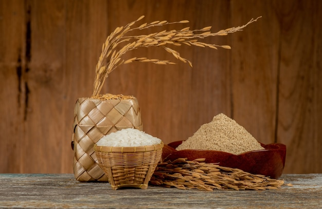 Jasmine rices,rice bran ,paddy and ear of rice on an old wood background.