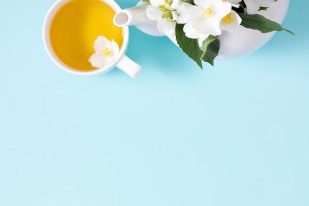 ジャスミン茶と花青い背景にジャスミンの花のティーポットフラットレイ