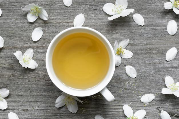 Жасминовый чай и цветы жасмина на деревенском деревянном фоне