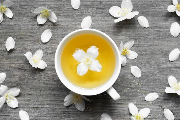 Чай жасмина и цветки жасмина на деревянной предпосылке.