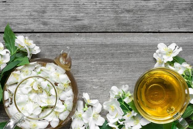 Жасминовый чай с цветами гороха и жасмина на деревянном фоне