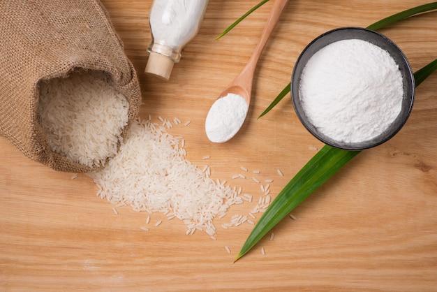 자루에 재스민 흰 쌀과 나무 테이블에 쌀가루.