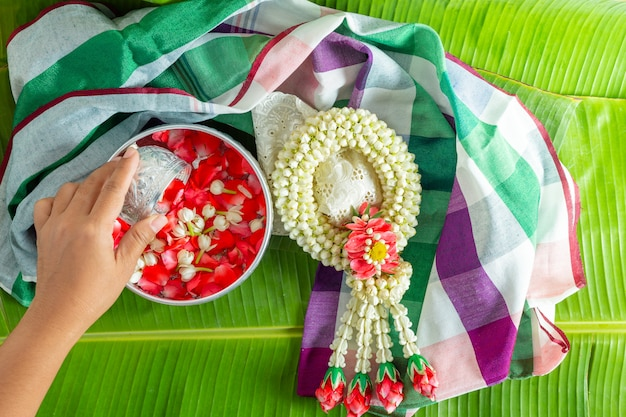 Jasmine and white rose garland on the background of green banana leaves.