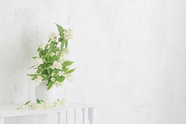 Жасмин в вазе на фоне старой стены