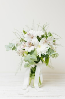 木製のテーブルの上の白いリボンとjasminum auriculatum花瓶