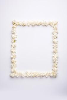 Жасмин самбак или цветок могра, расположенный в форме круглой или прямоугольной рамки на белом фоне, выборочный фокус