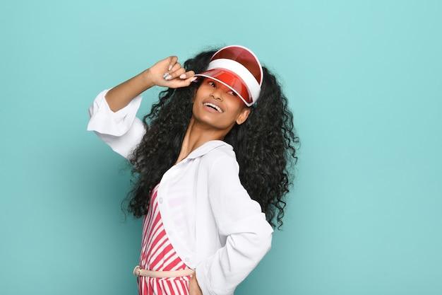 Бодрая счастливая молодая темнокожая женщина в красном винтажном козырьке позирует, оглядываясь через плечо с улыбкой на синем фоне