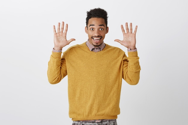 Lancette jazz sempre di tendenza. ritratto di giovane maschio emotivo felice con taglio di capelli afro che alza i palmi e sorride ampiamente, arrendendosi o esprimendo cordialità e buon umore