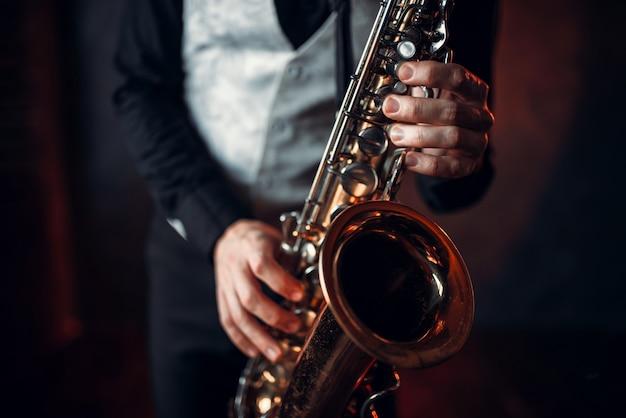 Jazz man hands holding saxophone closeup. brass band musical instrument.