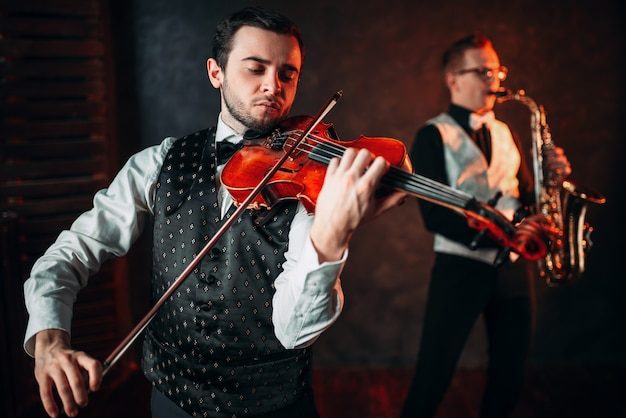 Jazz man and violinst, classical musical duet. sax and fiddle music players