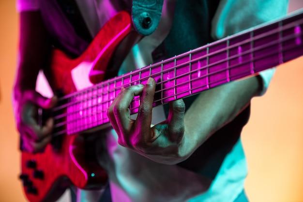 Джазовый музыкант играет на бас-гитаре в студии на неоновой стене