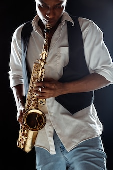 Jazz musician playing the saxophone in the studio on a black wall