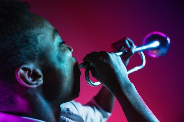 ネオンの壁のスタジオでトランペットを演奏するジャズミュージシャン