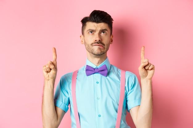 Ревнивый и грустный забавный мужчина в галстуке-бабочке, кусающий губу и искушенный промо-предложением, указывая пальцем вверх, стоит на розовом.