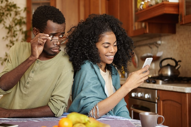 Ревнивый любопытный темнокожий мужчина держит очки, следящие за мобильным телефоном его подруги, пока она печатает сообщение для своего любовника и счастливо улыбается. предательство, неверность, неверность и недоверие