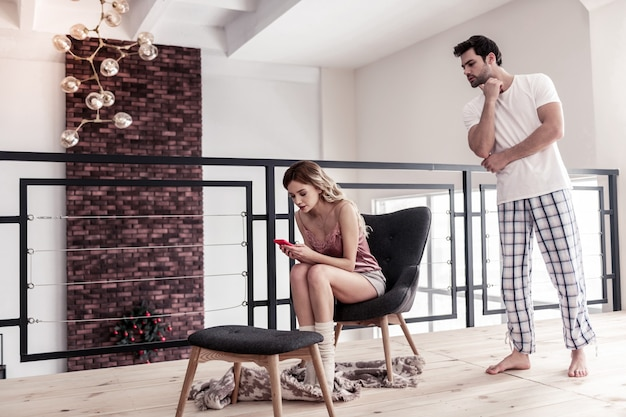Ревнивый муж. темноволосый бородатый молодой человек в белой футболке выглядит взволнованным, пытаясь прочитать сообщение на смартфоне своей жены