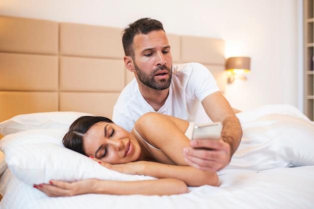 Ревнивый муж шпионит за телефоном своей партнерши, пока она спит в постели дома.
