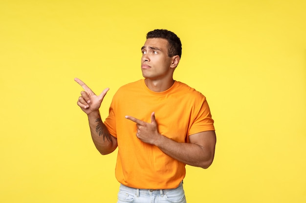 Jealous and upset gloomy cute masculine man, wear orange t-shirt, standing unhappy and sad over yellow background, sulking pointing and staring left with regret and uneasy feelings, yellow background
