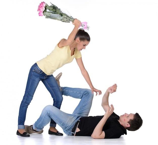 Jealous young woman beat her boyfriend bouquet of flowers.