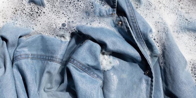 Джинсовая рубашка замачивает в растворе воды стирального порошка, стиральной ткани. концепция прачечной