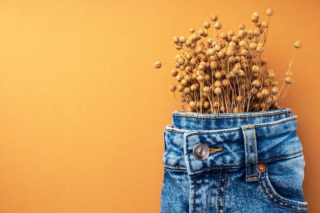 밝은 갈색 배경에 청바지와 마른 린넨. 천연 데님 패브릭 컨셉입니다. 데님 의류의 가을 패션 컬렉션. 재활용 소재로 만든 친환경 의류.