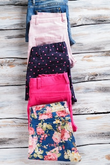 Джинсы и темно-синие брюки в горошек. сложенные брюки рядом с джинсами. подбор товаров в магазине. новая весенняя коллекция.