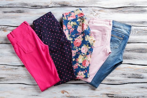 청바지와 바지. 컬러풀한 프린트의 라이트 팬츠. 봄을 위한 트렌디한 여성 의류. 점과 꽃.