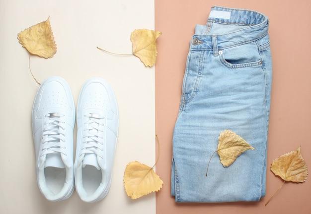 落ち葉の中のジーンズと白のスニーカー。ミニマリズム、トップビュー。
