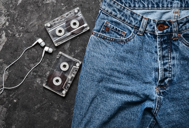 Jeans, audio cassette, headphones layout on a black concrete table. conceptual photo illustrating the fascination of listening to music. top view.