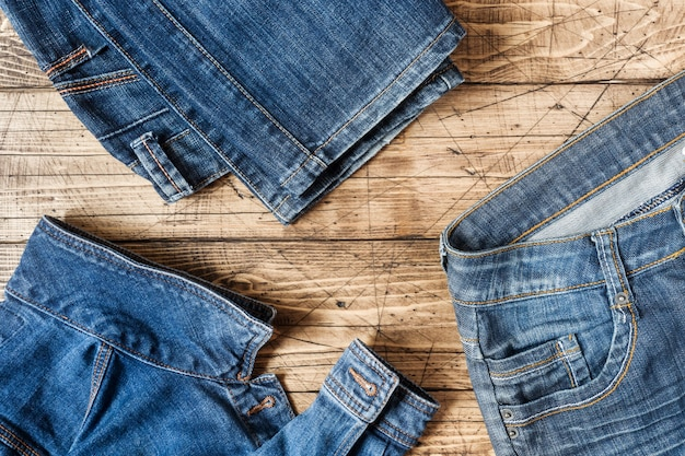 Jeans clothes and accessories on brown wood surface