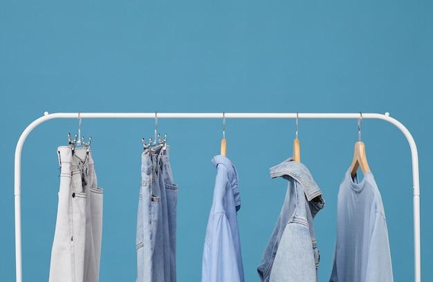 Джинсовая одежда висит на вешалке на синем фоне