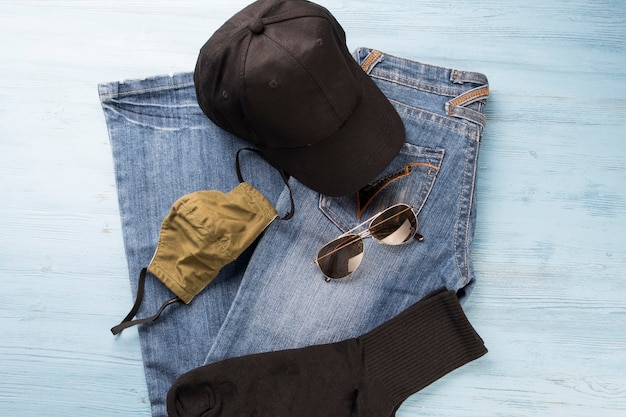 Jeans, face shield, socks and baseball cap on the table.